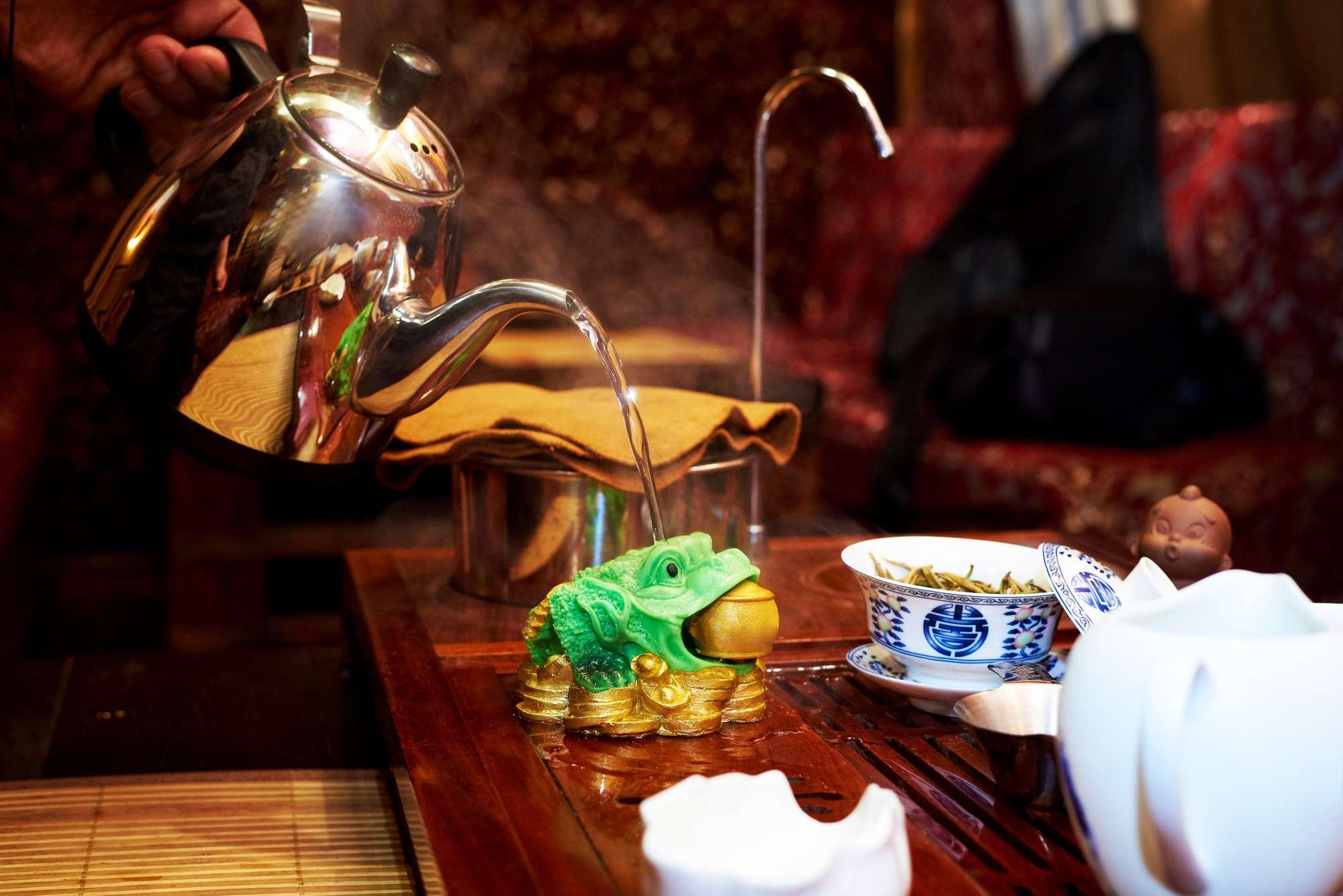 teaszertartás vörös bútorok között zöld békával