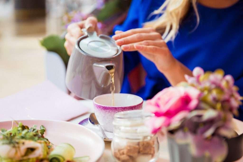 Teát töltő kékruhás nő.