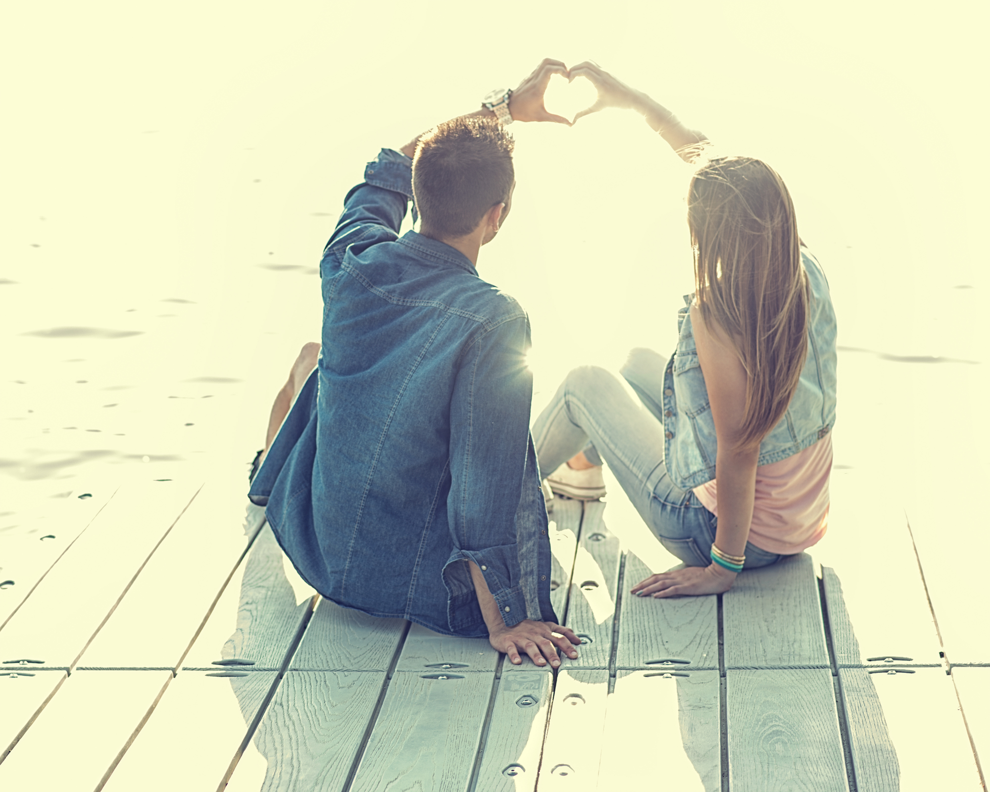napfenyben sutkerezo szerelmespar szivet formaz a kezevel