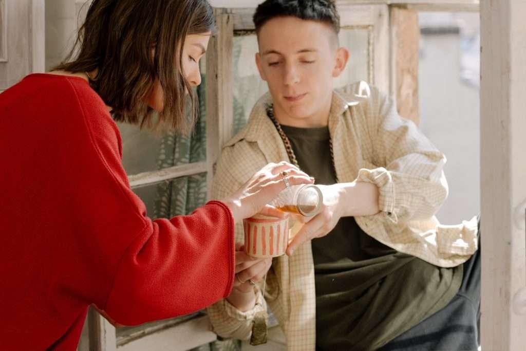 Napsütéses ablakban ülő fiatal férfinak teát tölt a barátnője.