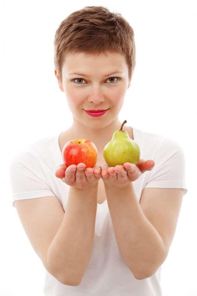 Almát és körtét tartó fiatal nő