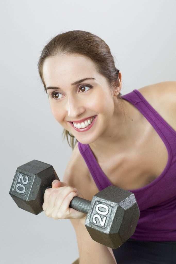 súlyzót emelő nő lila trikóban mosolyog