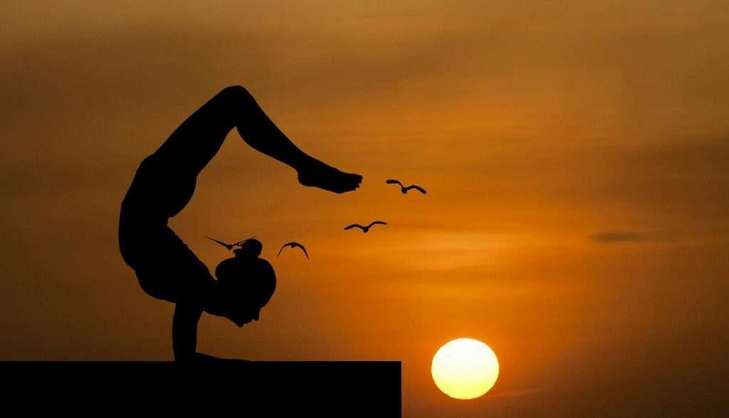 Jógázó lány sziluettje naplementében madarakkal