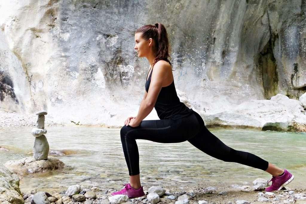 fiatal nő barlangban jógázik víz mellett